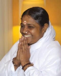 Amma is shown smiling with her hands in a prayer position.