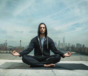 A man meditates against a city backdrop.