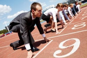 Following your heart is difficult because of the societal ideals that we learn about throughout life. A number of individuals, dressed in business attire, are lined up on the starting line of a track.