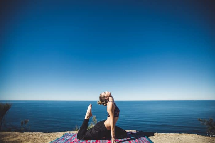 A woman is shown practicing yoga with the ocean in the background. Yoga is a key Ayurveda exercise that promote physical health.