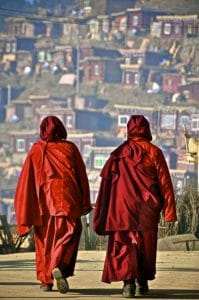 Two Buddhist monks are pictured walking in Larung Gar.