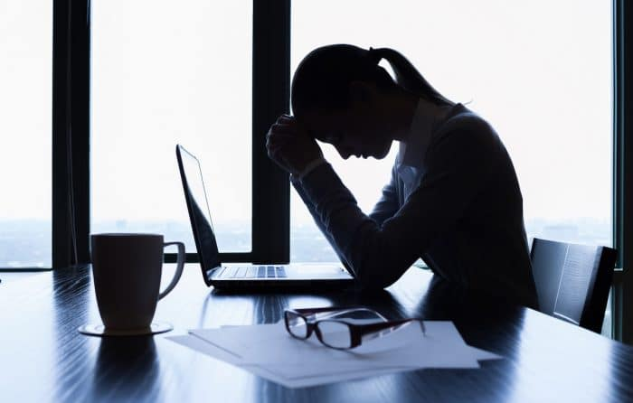 A stressed business woman is shown looking at her laptop with her head in her hands. Has she defined what success is?