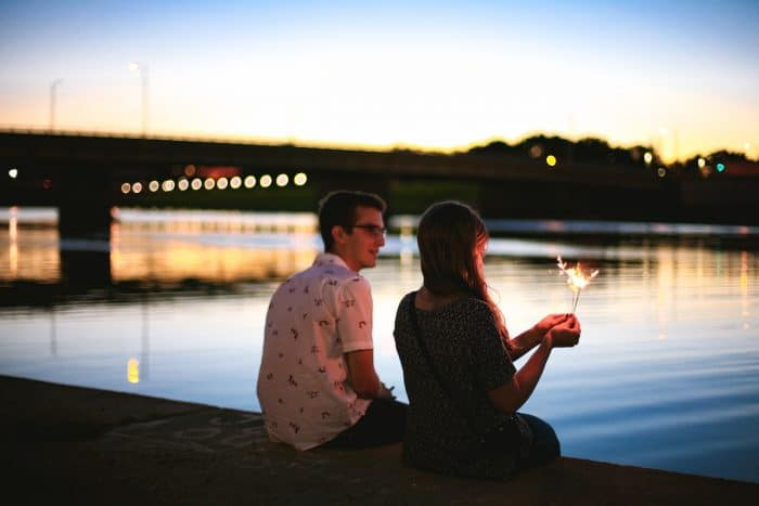 A smiling couple sits on the side of a river laughing with a sparkler. What is Success to them?
