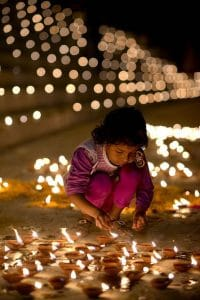 A young girl is seen lighting a candle on Diwali. Around her are many more candles already lit.