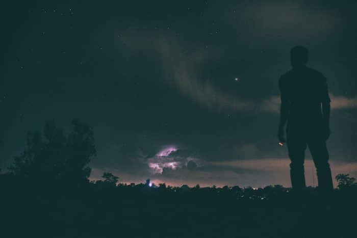 A man looks at a passing storm. This picture represent the idea that individuals can watch anxiety come and go like the changing weather.