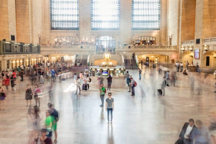 A time-lapsed photo of a train station is shown with many blurred figures moving and one man clearly shown standing still in the middle. The photo represents the need to be grounded to overcome the habit of judging others.