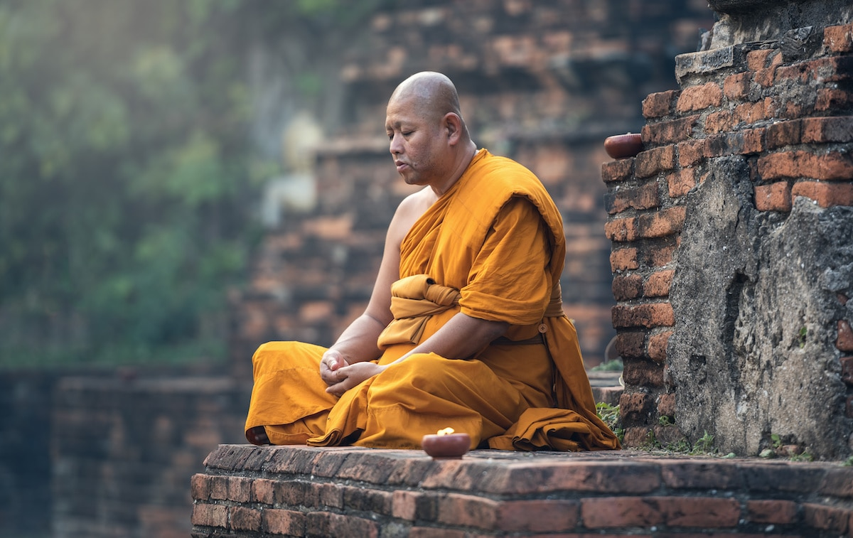 A Buddhist Monk Is Shown Meditating Outside Of Temple He Assuredly Using