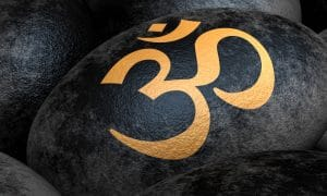 A black rock is shown with the Om symbol painted in gold on it.