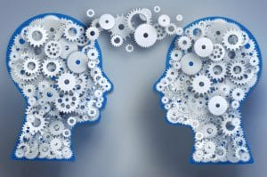 A computer generated image is shown of two heads filled with metal gears. The gears are connecting the two heads and serves as a metaphor for empathy.