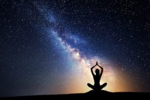 A silhouette of a woman is shown in a meditation posture against a expansive sky. A particular star pattern is shining down and illuminating her. This picture represents the idea that consciousness is the key to taking care of the mind, body, and soul.