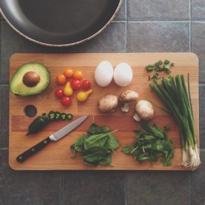 A cutting board is shown with a variety of healthy vegetables on it.
