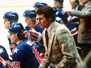 An image of the 1980 United States Olympic hockey coach Herb Brooks is shown while coaching on the bench.