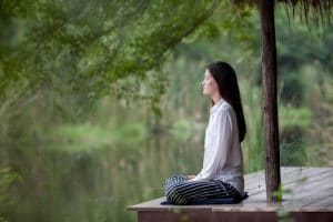 An image is shown of a woman meditating next to lake. Her eyes are closed and she is using the meditation components of mindfulness and concentration.
