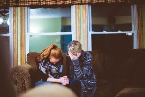 An image shows a daughter and mother sitting on their couch crying with their heads down. It seems as if a tragic event has taken place in their lives which according to CBT can lead to a downward spiral towards negative mental health disorders.