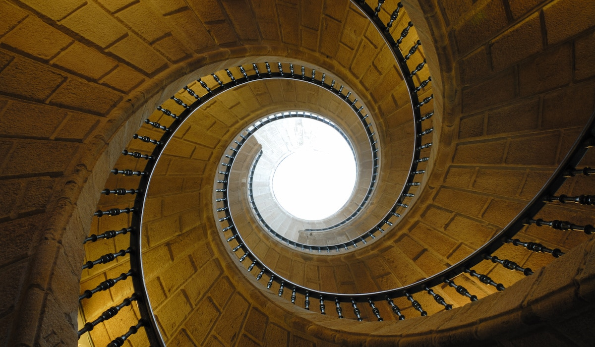 A Beautiful Spiral Staircase Is Shown From The Bottom Floor Of A Building  Looking Up At