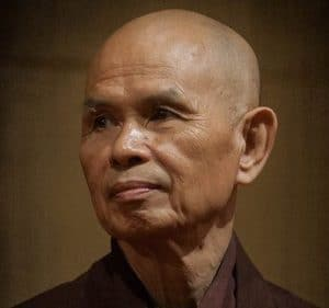 A headshot of Thich Nhat Hanh shows the celebrated Buddhist monk in traditional robes.