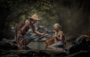 Two Asian women are shown washing clothes in a river with big smiles on their face. One woman is handing the other something she found of her's. This picture represents the idea that we can make each day memorable by small acts of love and compassion.