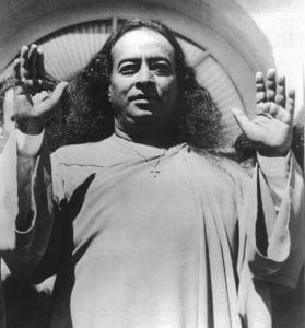 An image shows Hindu sage Paramahansa Yogananda speaking with his hands in the air.