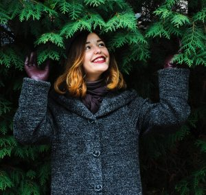 A young woman is seen standing under a pine tree with a big smile on her face. This image represents the idea that we can transform our core beliefs so that they serve us better.