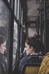 A young woman is seen riding on a bus as she looks out the window. From the perspective of the photographer, you can also see this woman's reflection. The image represents the idea that core beliefs we hold about ourselves are dependent upon how we perceive ourselves to be.