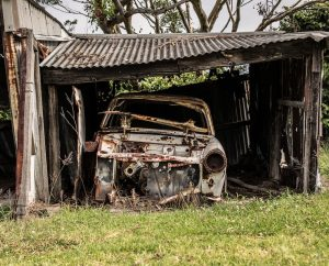 An image shows a rusty broken down car sitting in a broken down garage which illustrates the fact that we cannot win the game of real life by chasing the impermanent.