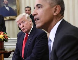 An image shows Donald Trump looking skeptically at Barack Obama as he talks to reports. Since coming to Washington, Trump has been quick to blame Obama for all of his failings.