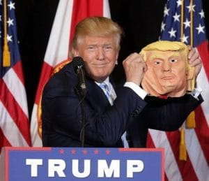 An image shows Donald Trump holding up a mask of himself during the 2016 election. This picture is featured in Balanced Achievement's article on his psychological mindset. It was taken by Chip Somodevilla and Getty Images.