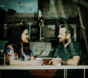 An image shows a couple sitting inside a coffee shop having a conversations and smiling at one another. The image represents the idea that we can improve our relationships by skillfully asking questions.