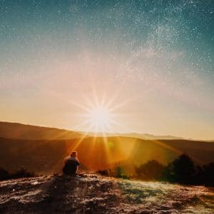 An image shows a man sitting on a hill with an awe-inducing sunset in the background and a starry sky above that. This image represents the idea that we can change our lives by transforming our cognitive schemas.
