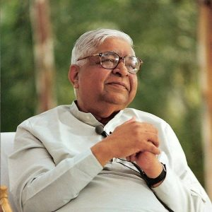 A portrait style image shows S.N. Goenka sitting peacefully with his hands together above his chest.