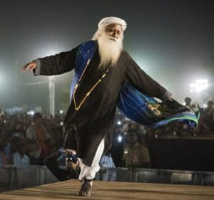 An image shows the great Hindu sage Jaggi Vasudev dancing exuberantly at the 2017 Mahashivratri festival.