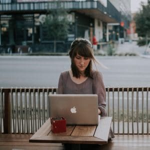 A young woman is shown contentedly working on her laptop on the patio of a cafe. This image represents the idea that balance is key to strive for more and achieve life's ultimate aim of finding enjoyment in the days.