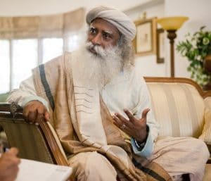 An image shows the iconic Hindu sage Sadhguru talking to a reporter as he sits in a chair.