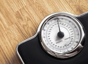 An image shows a weight scale on a wooden floor.