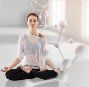 An image shows a young women practicing meditation with a scientific gene graphic superimposed on the image. This picture represents the science of Mindfulness-Based Stress Reduction (MBSR).