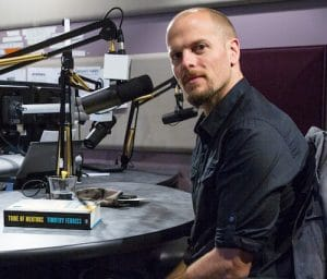 An image shows inspirational icon Tim Ferriss in his podcast studio with a copy of his book 'Tribe of Mentors' in front of him on a table.