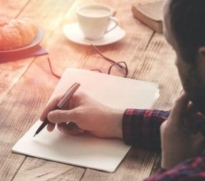 An image shows a man writing in a notebook with a cup of coffee and croissant, as the morning sun shines on his table. This picture is featured in Balanced Achievement's article on empowering morning questions.