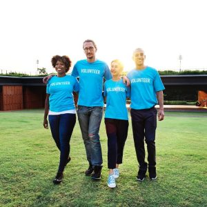 An image shows four volunteering walking arm and arm as the sun shines down on them. This picture is used in Balanced Achievement's article on integrity and intelligent effort to show why acting upon our moral compass within is vital to achieve world changing success.