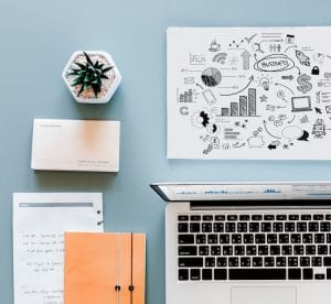 An image shows a neatly organized desk with a computer, plan, notebook and cartoonish diagram showing the way to success. This picture represent the idea that intelligent effort is necessary to change the world.