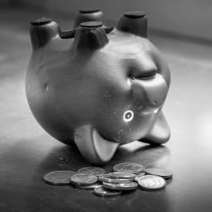 An image shows a piggy bank upside down on table with loose change next to it to illuminate financial problems and debts. This image is used in Balanced Achievement's article looking at mindful money management.