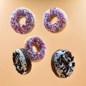 An image shows 6 donuts falling from the sky. This picture represents the idea that the ways we think our pleasure are illusionary in Balanced Achievement's article on natural selection and life satisfaction.