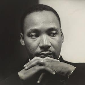 An image shows the one and only Martin Luther King Jr. sitting with his hands folded together near his face as he looks as if he's in deep thought. This picture is used in Balanced Achievement's article covering 20 Martin Luther King Jr. quotes.